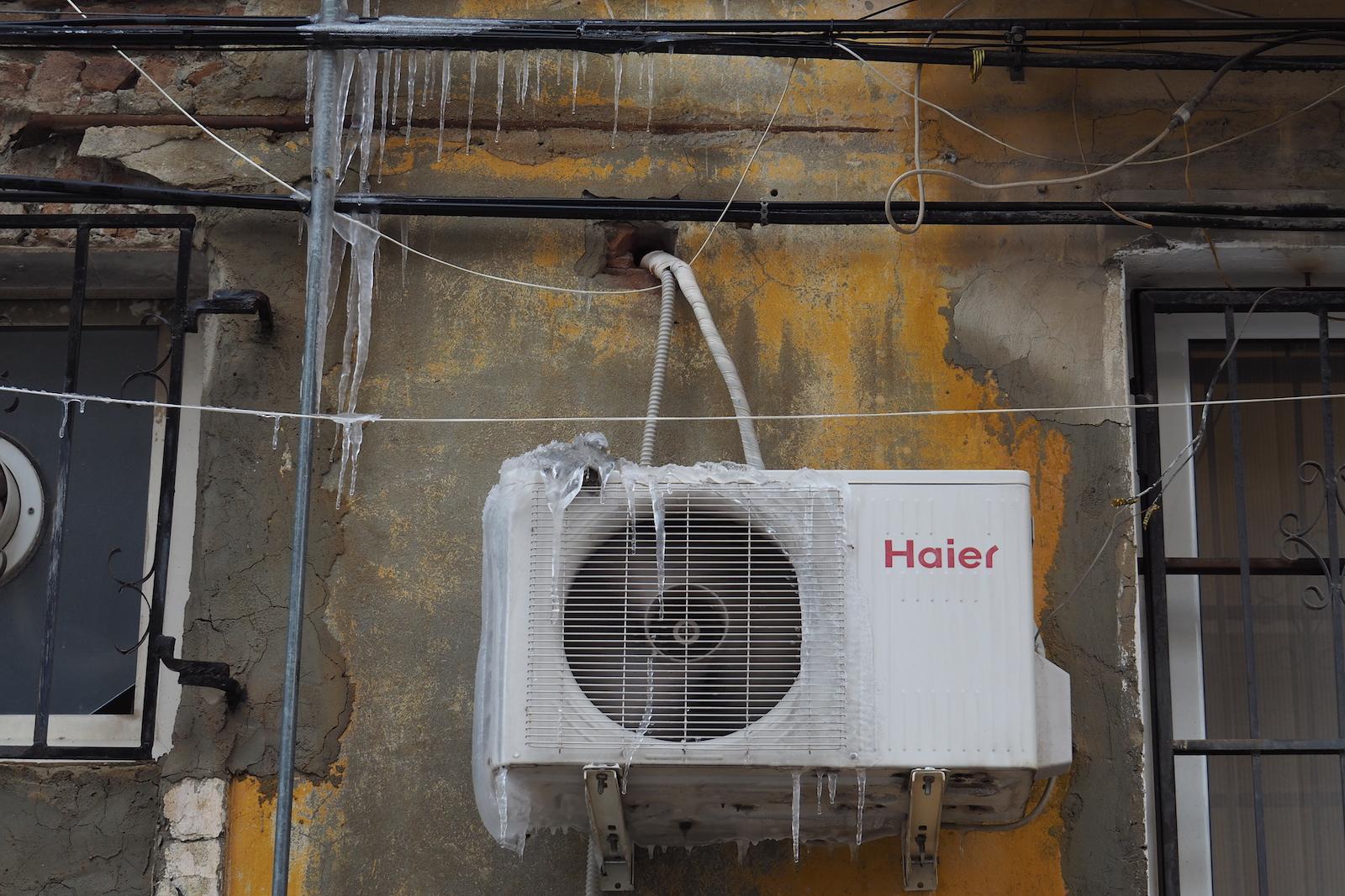 Klimaanlage an der Hauswand, von Eis bedeckt.